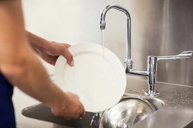 Kitchen porter cleaning white plates in sink Premium Photo