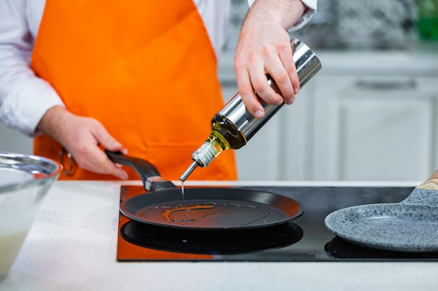 Kitchen preparation: the chef pour oil in a frying pan Premium Photo