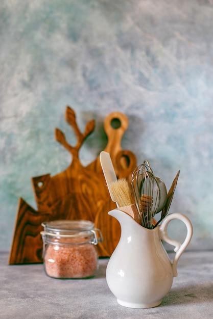 様々なハーブ、スパイス、種子、豆類、まな板、白の調理器具が付いている台所の棚 無料写真