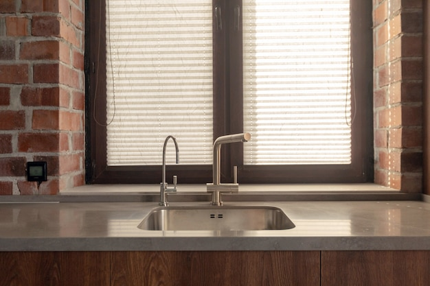 Kitchen sink with few faucets next to window and brick wall Premium Photo