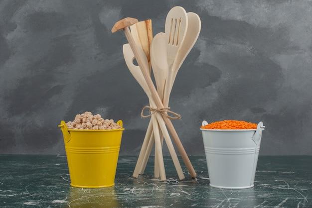 Utensili da cucina con due secchi colorati di noci sulla superficie in marmo Foto Gratuite