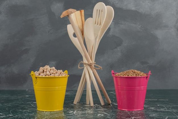 Utensili da cucina con due secchi colorati di noci sul tavolo di marmo. Foto Gratuite