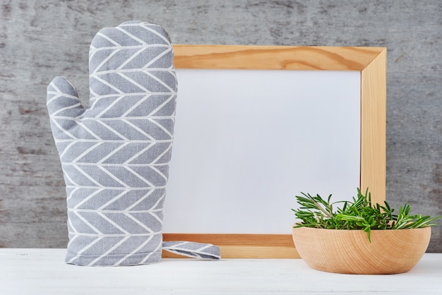 Kitchen utensils background with empty white paper, potholder and bowl with rosemary on a white table Premium Photo