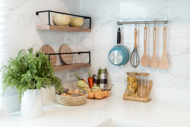 Kitchen wood utensils, chef accessories. hanging copper kitchen with white tiles wall. Premium Photo