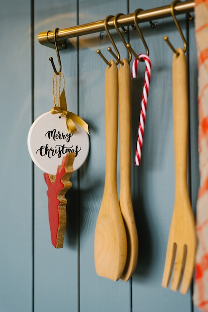 Kitchen wooden spatulas and fork vit on a hook in the kitchen, cooking accessories, and christmas tree toys Premium Photo