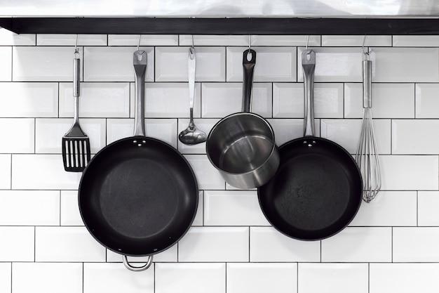 Kitchenware hanging on a white brick wall Premium Photo