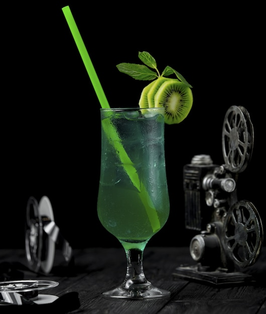 Kiwi alcohol cocktail with fruit slices and green pipe. Free Photo