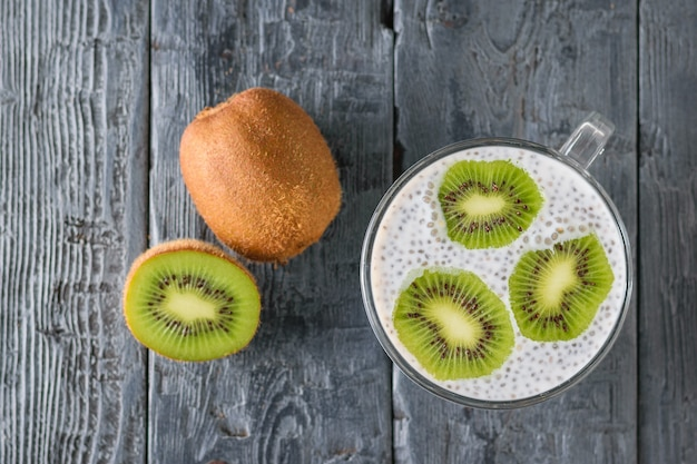 Kiwi fruit and a mug of black chia seed pudding on a black wooden table. the view from the top. flat lay. Premium Photo