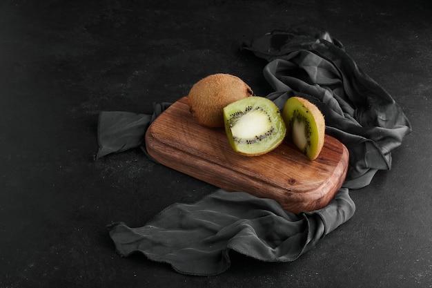 テーブルクロスの木の板にキウイ。 無料写真