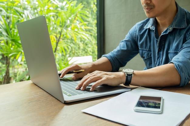スマートフォンとテーブルの上の書類とklaptopに取り組んでいるカフェに座っているビジネスマン Premium写真