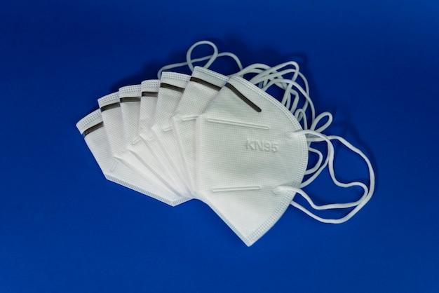 Белая маска kn95 или n95 с противовирусной медицинской маской для защиты от коронавируса на синем Premium Фотографии