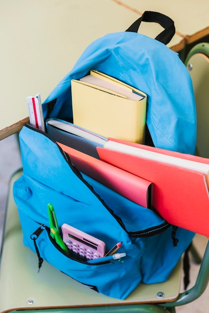 Knapsack with books on chair Free Photo