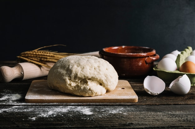 Knead dough with ingredients on wooden table Free Photo