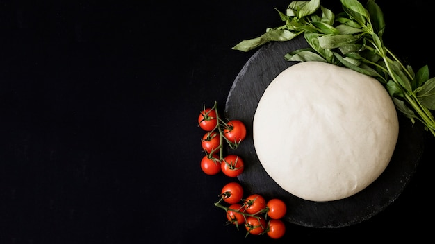 Kneaded uncooked dough; red cherry tomatoes and basil on slate against black background Free Photo