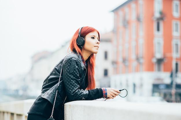 Knee figure of young beautiful hispanic redhead woman listening music with headphones Premium Photo