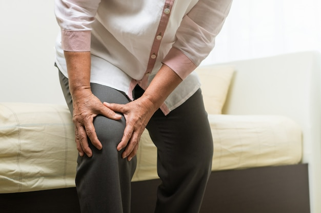 Knee pain of old woman at home Premium Photo