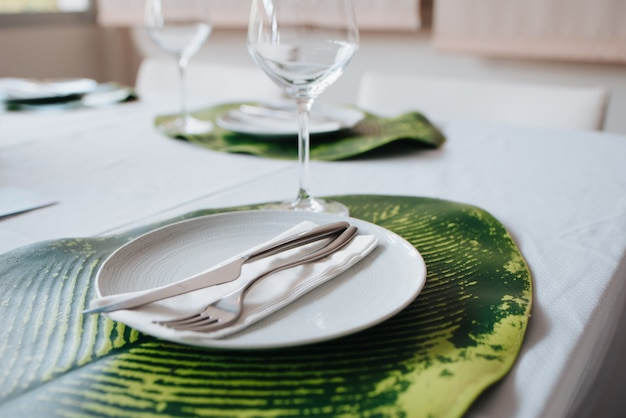 Knife and fork placed on a napkin on a white plate. placed on a sheet for a wedding Premium Photo