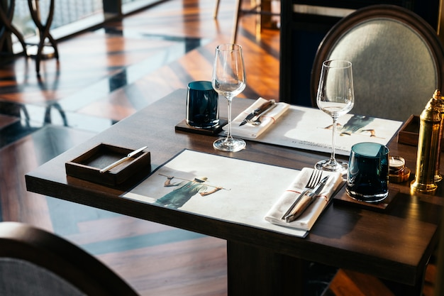 Knife and fork with napkin on wooden table for fine dining Premium Photo