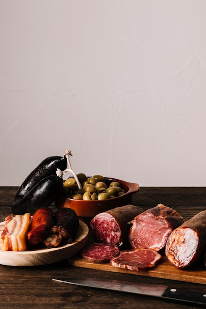 Knife near sausages and olives Free Photo