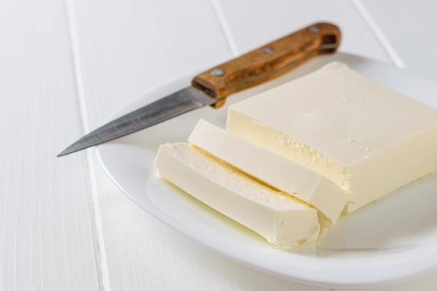 A knife with a wooden handle next to a sliced piece of serbian cheese. Premium Photo