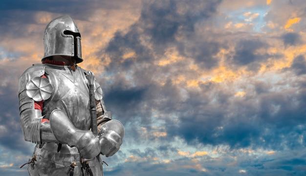 Knight in helmet and metal armor. Premium Photo