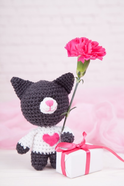 Knitted cat with a heart. st. valentine's day decor. knitted toy, amigurumi. valentines day greeting card. Premium Photo