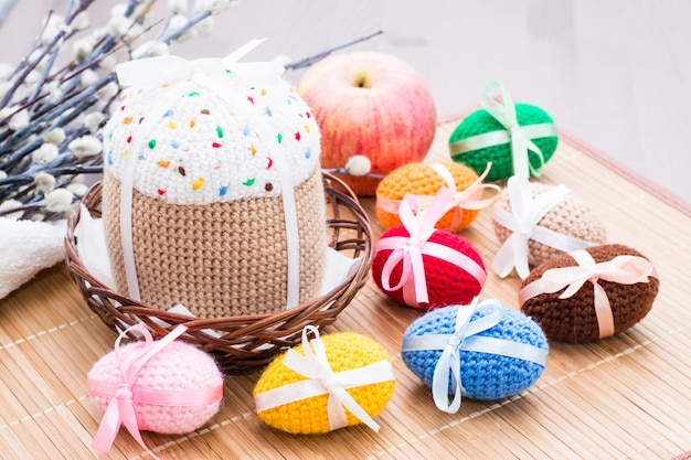 Knitted easter eggs and cake in a basket and willow on a wooden table Premium Photo