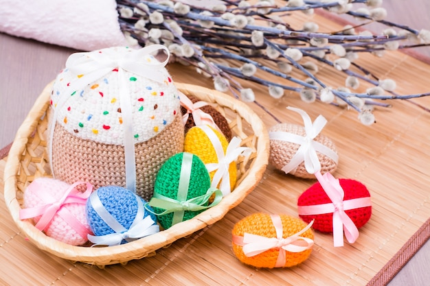 Knitted easter eggs and easter cake in a wicker basket on a wooden table Premium Photo