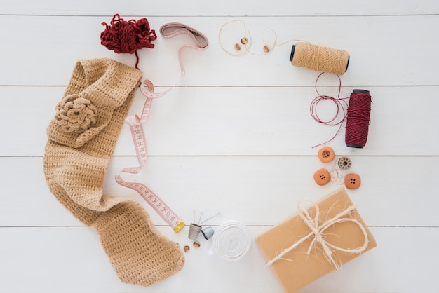 Knitted hosiery; wool; measuring tape; spool; button; wrapped gift box on wooden desk Free Photo