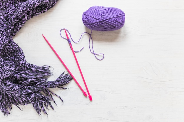 Knitted needles with purple yarn and scarf on white textured backdrop Free Photo