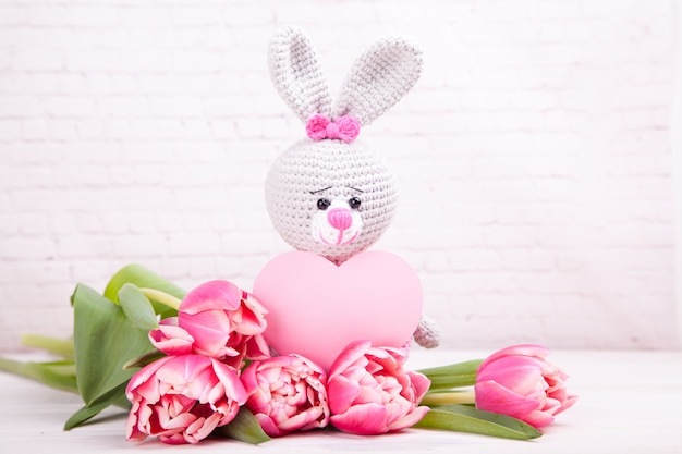 Knitted rabbit. festive decor. delicate pink tulips. valentine's day. handmade, knitted toy, amigurumi Premium Photo