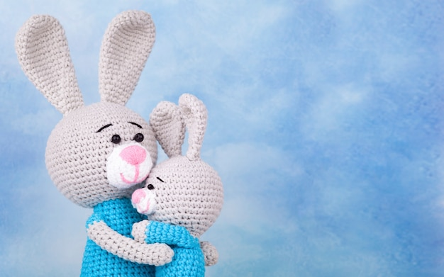 Knitted rabbits - mom and son with gifts and flowers. knitted toy, handmade, amigurumi, creativity, diy. mothers day card Premium Photo