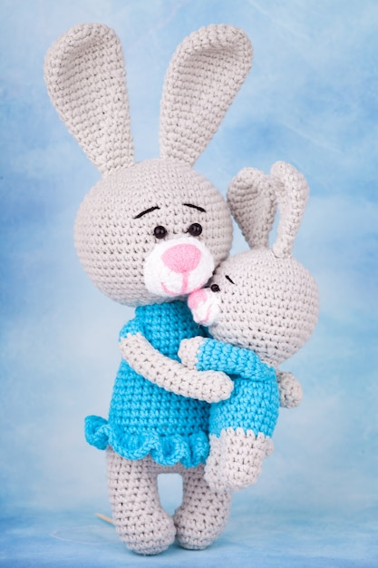 Knitted rabbits - mom and son with gifts and flowers. Premium Photo