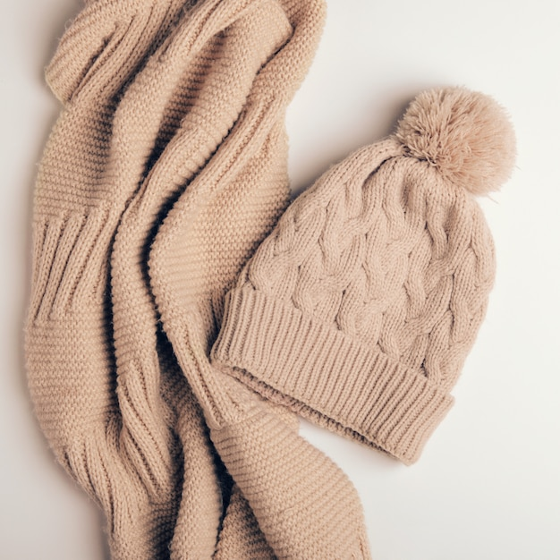 Knitted scarf a pipe from warm threads and beige cap with a