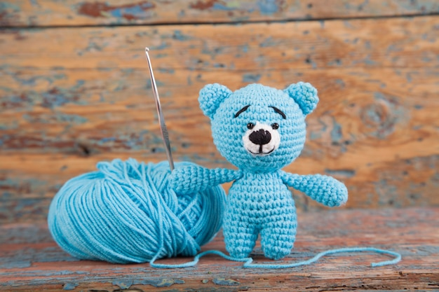 Knitted small bear on an old wooden background. handmade, knitted toy. amigurumi Premium Photo