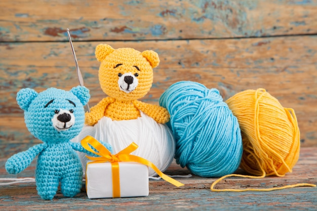 Knitted small bears on an old wooden background. handmade, knitted toy. amigurumi Premium Photo