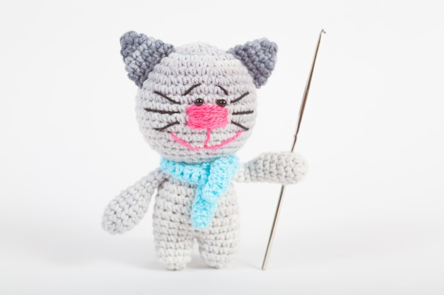 Knitted small cat on an white . handmade, knitted toy. amigurumi Premium Photo