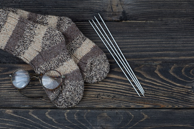 Knitted socks, knitting needles and old glasses Premium Photo