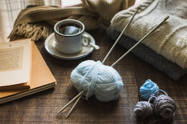 Knitting supplies near hot beverage and books Free Photo
