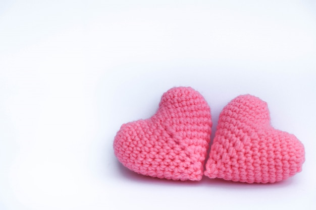 Knitting yarn crochet hearts shape pink color handmade cute pattern on isolate background Premium Photo