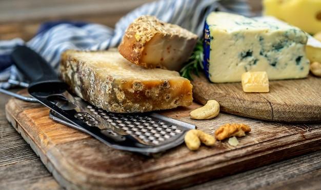 ナイフと木の板にさまざまなチーズ Premium写真