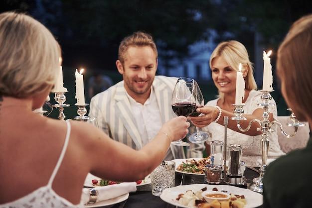 グラスをワインでたたく。エレガントな服装の友人のグループが豪華なディナーを持っています 無料写真