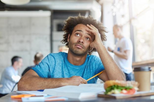 Conoscenza ed educazione. studente universitario afroamericano infelice che indossa la maglietta blu che osserva in su con espressione frustrata discutibile, sentendosi stanco mentre lavora sull'assegnazione domestica al caffè Foto Gratuite