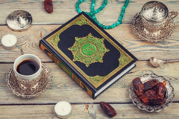 Koran book with dates and coffee cup Premium Photo