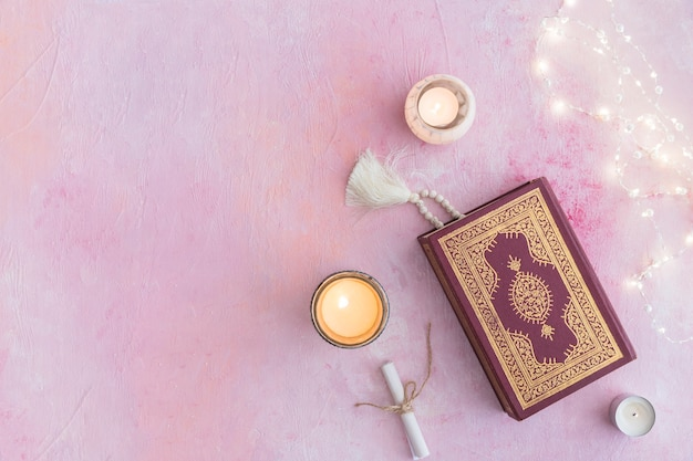 Koran with beads and candles Free Photo