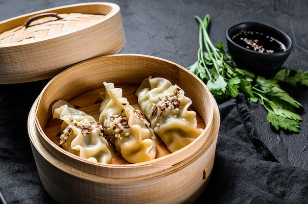 Korean dumplings in a traditional bamboo steamer. top view. rustic old vintage black background Premium Photo