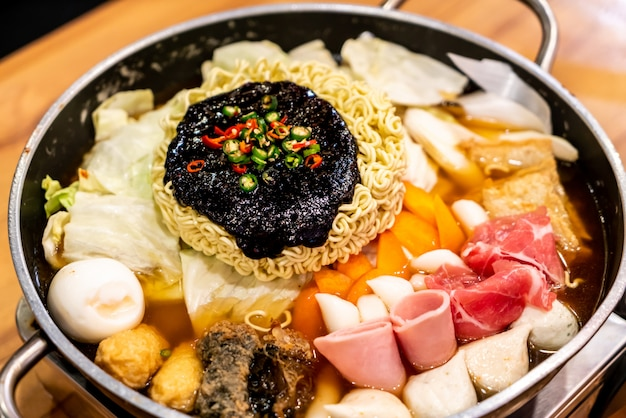 Korean hot pot 'budae jjigae' is korean fusion food incorporates american style with noodle, ham, sausages, and kimchi. Premium Photo