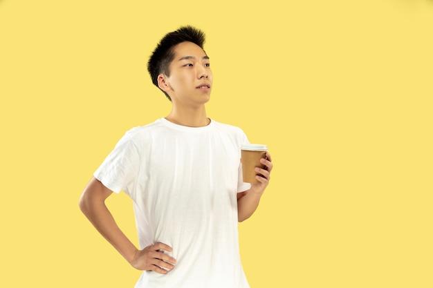 Ritratto del giovane coreano. modello maschile in camicia bianca. bere caffè, sentirsi felici. concetto di emozioni umane, espressione facciale. vista frontale. colori alla moda. Foto Gratuite
