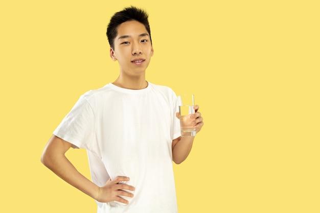 Ritratto del giovane coreano. modello maschile in camicia bianca. bevendo acqua. concetto di emozioni umane, espressione facciale. vista frontale. colori alla moda. Foto Gratuite