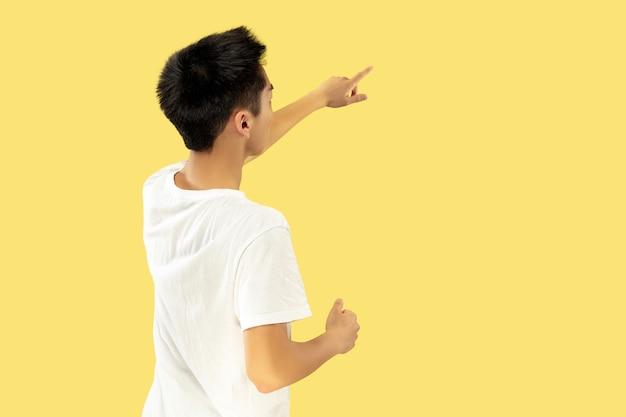 Ritratto del giovane coreano. modello maschile in camicia bianca. indicando il luogo per il tuo annuncio. concetto di emozioni umane, espressione facciale. colori alla moda. Foto Gratuite